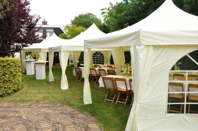 Opgezette tenten met tafels bij tuinfeest