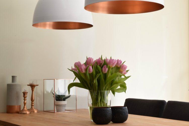 Witte lampen met koperen binnenzijde boven eettafel