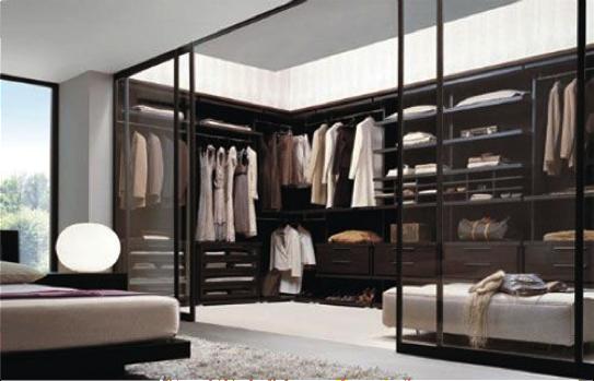 Mooie walk-in closet achter glazen schuifdeuren